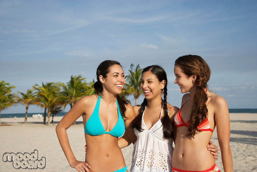Three teenage girls (16-17) wearing bikinis standing on beach portrait