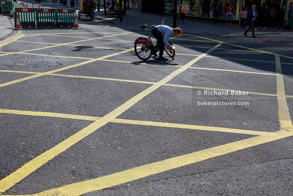A cyclist bends to retrieve dropped items on a box junction in the middle of Oxford Street, on 5th June 2019, in London, England.