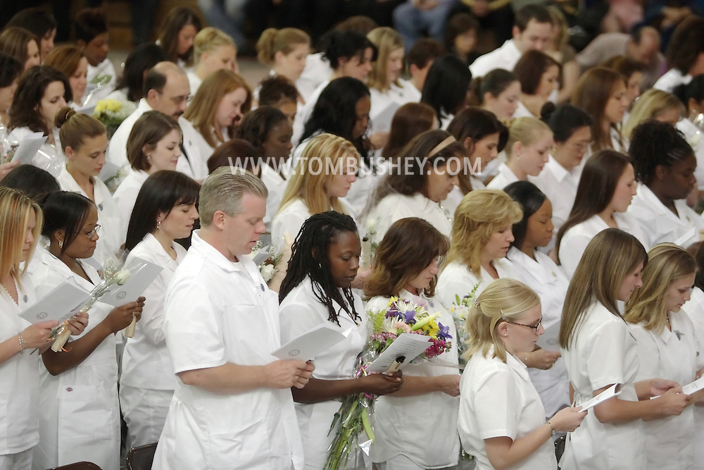 Middletown, NY - Nursing students read from their programs during the pinning ceremony for nursing graduates at Orange County Community College on May 17, 2007.