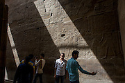 Egyptian tourists take selfies under sunlit hieroglyphs in the dark recesses of the ancient Egyptian Luxor Temple, Nile Valley, Egypt. The temple was built by Amenhotep III, completed by Tutankhamun then added to by Rameses II. Towards the rear is a granite shrine dedicated to Alexander the Great and in another part, was a Roman encampment. The temple has been in almost continuous use as a place of worship right up to the present day.