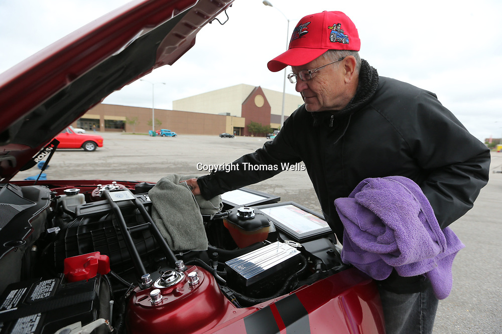 Norman Hass of Verona makes one final pass with a towel over the engine of his Rouse Racing Ford Mustang he brought to this year's Blue Suede Cruise on Friday.