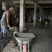OCTOBER 13 - UTUADO, PUERTO RICO - <br /> Pedro Cortez, 63, shelves mud to dump mud into the Tanama river in downtown Utuado after the path of  Hurricane Maria. The mud came from Cortez's home which was flooded by the river.<br /> (Photo by Angel Valentin/Freelance)
