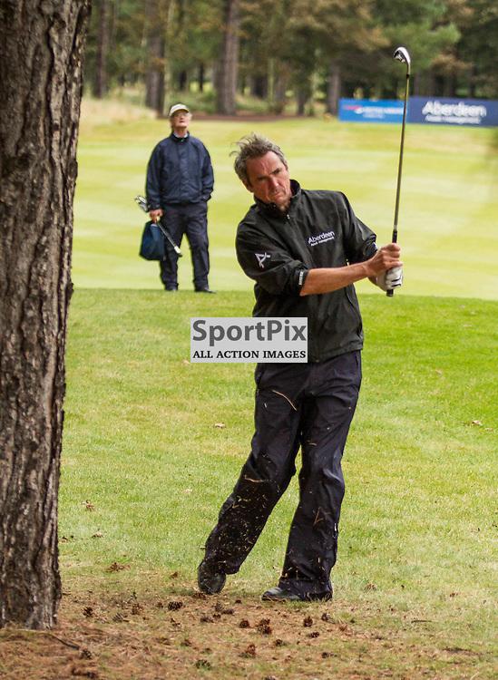 ex-football pundit Alan Hansen hits from the trees at the 9th hole. Aberdeen Asset Management Ladies Scottish Open (c) [Neil Bain] | SportPixPix.org.uk