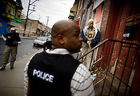 U.S. Dept. of Housing and Urban Development Special Agent Donrich Young, left, and Philadelphia Police Detectives Robert Richardson, center, and Michelle Haines, try to serve a warrant in South Philadelphia on Friday, Feb. 3, 2006. Photo by Ryan Donnell