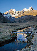 "At sunrise, a stream flows through Tuctucpampa campground below Nevado Jirishanca (left, ""Icy Beak of the Hummingbird"" 6094 m) and Rondoy (right 5870 m). Day 2 of 9 days trekking around the Cordillera Huayhuash, in the Andes Mountains, Peru, South America."