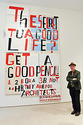 """© Licensed to London News Pictures. 04/09/2018. LONDON, UK.  Celebrated artist Bob and Roberta Smith RA, poses with his new work """"The Secret of a Good Life"""", the first display by a Royal Academician in the new Ronald and Rita McAulay Gallery, a new space dedicated to site-specific installations by Royal Academicians in the new Royal Academy in Piccadilly.  This and other works are on display 4 September to 3 February 2019.  Photo credit: Stephen Chung/LNP"""