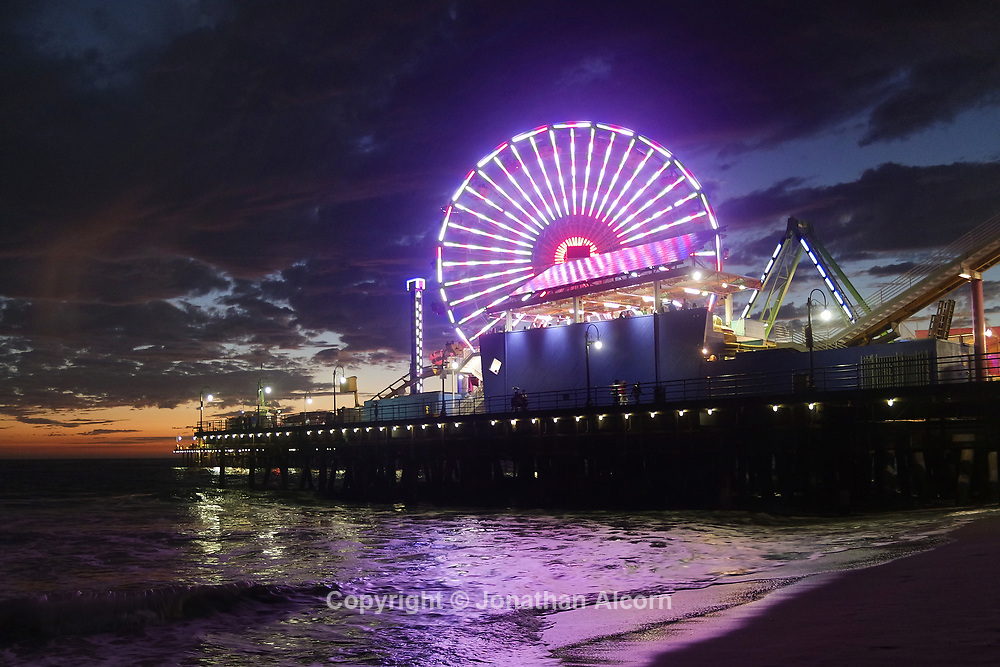 Light from the Pacific Wheel reflects on the sand at the Santa Monica pier.