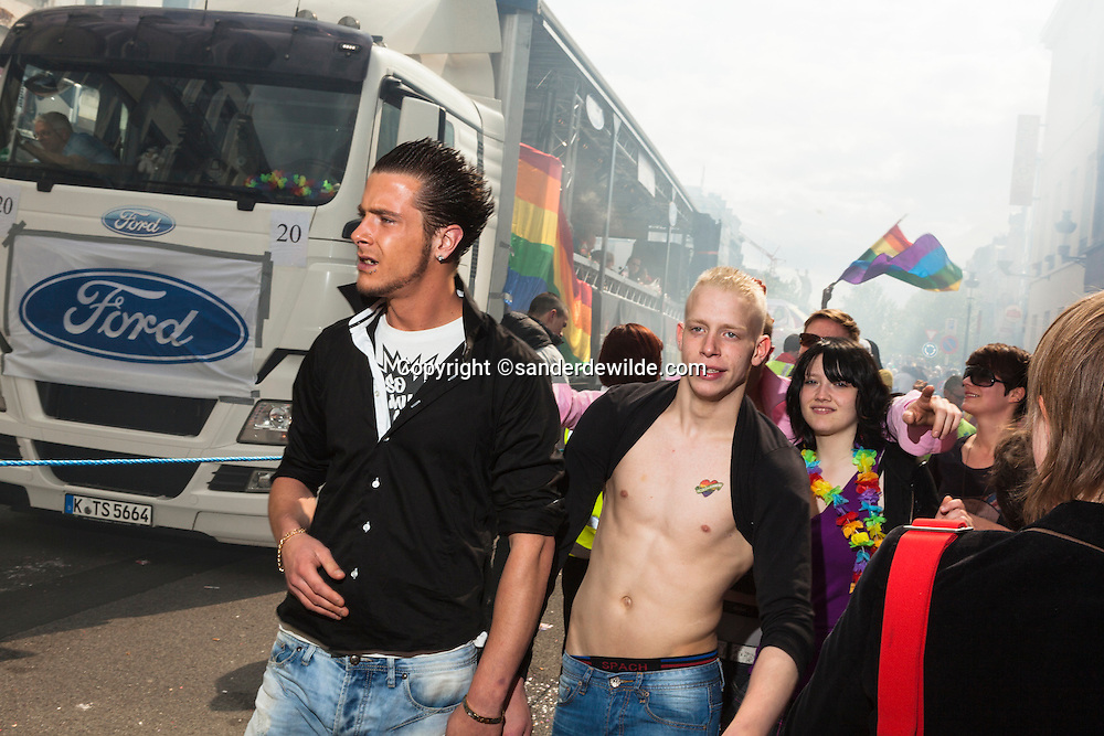 Participants of a gay pride parade in Brussels next to a Ford truck. Guy with naked torso