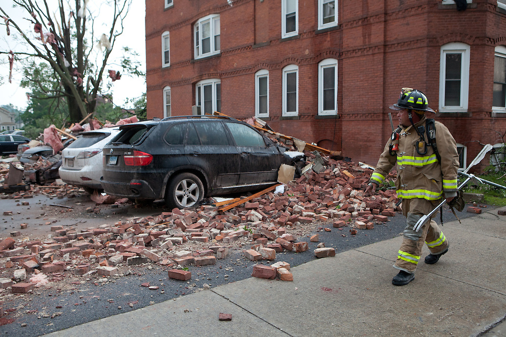 A firefighter walks past damaged cars in downtown Springfield, MA where a tornado struck on Wednesday afternoon June 1, 2011.  (Matthew Cavanaugh for The Boston Globe)