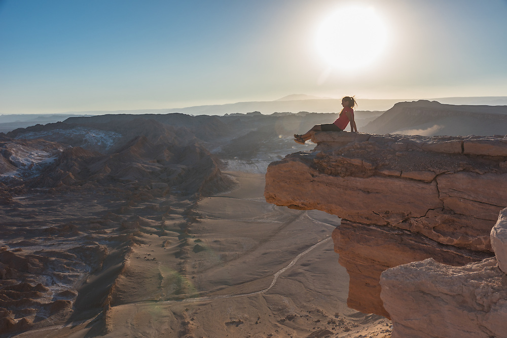 Woman sits on a big boulder at sunset in the Valley of the Moon, Chile.