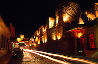 Car lights streak down a cobblestone street in fornt of the Santa Catalina Arch in Antigua (La Antigua Guatemala), Guatemala
