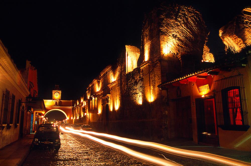 Car lights streak down a cobblestone street in fornt of the Santa Catalina Arch in Antigua (La Antigua Guatemala), Guatemala