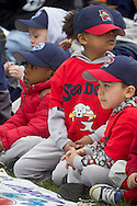 Middletown, New York - Young baseball players sit on the field after marching in the 60th annual Middletown Little League parade on April 14, 2013.