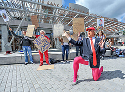 Roland Saunders as Donald Trump highlights his show outside the Scottish Parliament, aided by members of the public.<br /> <br /> &copy; Dave Johnston/ EEm