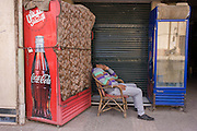 An Egyptian man sleeps awkwardly in a chair alongside a Coca-Cola dispenser in the modern city of Luxor, Nile Valley, Egypt.