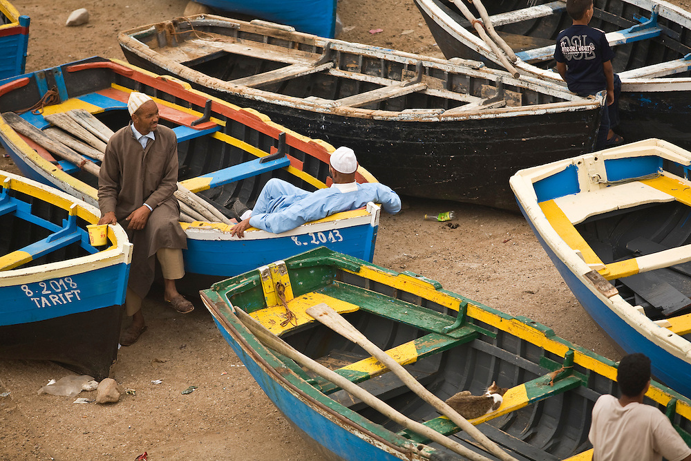 People sitting on colorful fishing boats on the beach in Taghazout, Morocco.Taghazout is a popular surfing town north of Agadir.