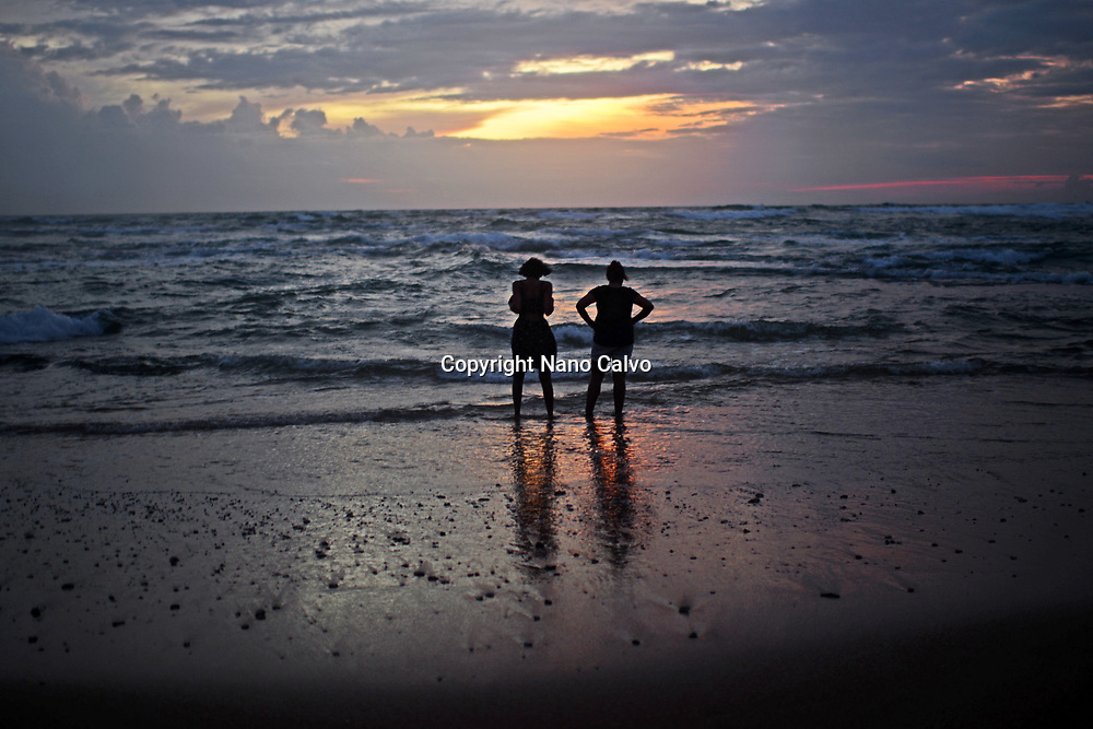 Two women relaxing on Hikkaduwa beach at sunset, Sri Lanka