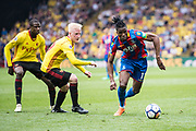 Wilfried Zaha (11) of Crystal Palace, Watford (19) Will Hughes, Watford (16) Abdoulaye Doucouré  during the Premier League match between Watford and Crystal Palace at Vicarage Road, Watford, England on 21 April 2018. Picture by Sebastian Frej.