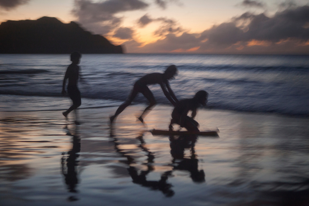 FERNANDO DE NORONHA, BRAZIL: Kids playing bodyboard on the shore of the beach at sunset in Fernando de Noronha, Brazil.