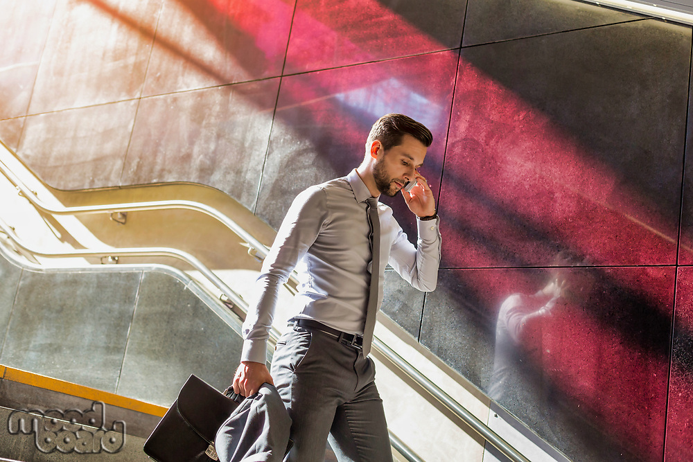 Portrait of young attractive businessman talking on smartphone while walking downstairs