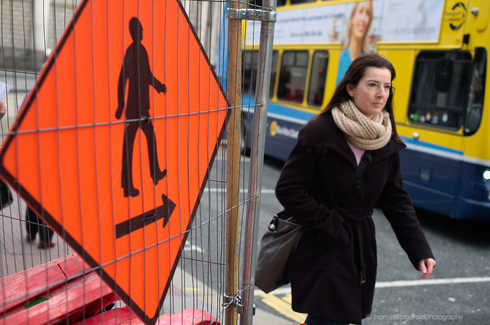 A woman walks past a diversion sign during the construction of the Luas Cross City project.