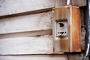 An old, rusted electrical box on the outside wall of a wooden building. Missoula Photographer