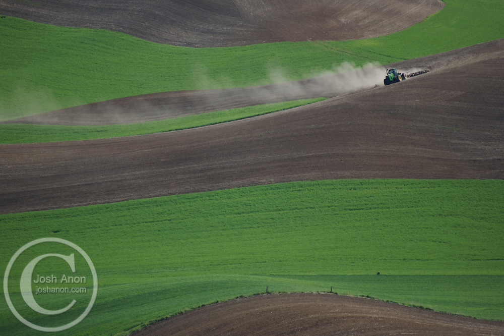 A farmer and tractor work a field in the Palouse area, Washington.