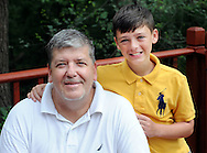 Jeffrey Gunn (left, poses with his son Colt Gunn, 11 years old Friday June 19, 2015 in Bensalem, Pennsylvania. For the past 15 years, Gunn has worked out of his home in his job with Meridian. (Photo by William Thomas Cain)