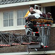 Zwangere vrouw word met behulp van een brandweer ladderwagen op een brancard uit huis gehaald Koninging Julianastraat Huizen