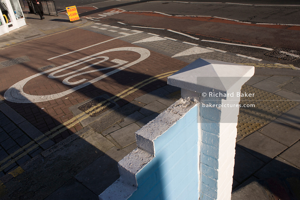 The various lines and markings with a 20mph speed zone warning, on an urban road junction.