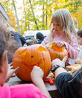 Lily and Kendall carve out pumpkin faces at the Laconia Boys and Girls Club on Tuesday afternoon.  Approximately 60 pumpkins will be added from the Boys and Girls Club for Saturday's Pumpkin Fest.    (Karen Bobotas/for the Laconia Daily Sun)