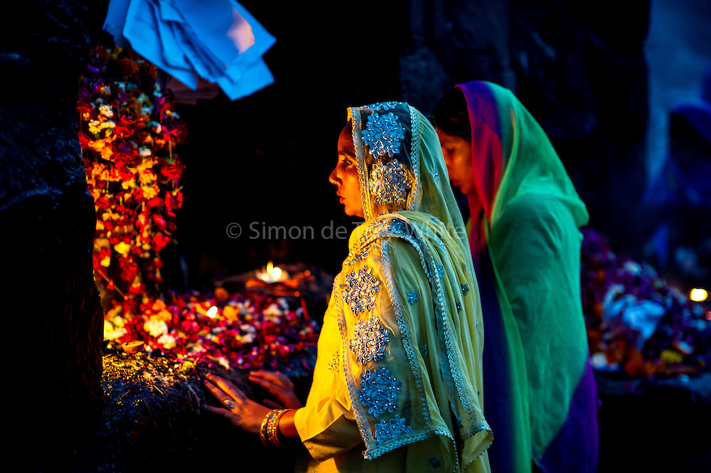2nd April 2015, New Delhi, India. Women pray at a shrine dedicated to Djinn worship in the ruins of Feroz Shah Kotla in New Delhi, India on the 2nd April 2015<br /> <br /> PHOTOGRAPH BY AND COPYRIGHT OF SIMON DE TREY-WHITE a photographer in delhi<br /> + 91 98103 99809. Email: simon@simondetreywhite.com<br /> <br /> People have been coming to Firoz Shah Kotla to leave written notes and offerings for Djinns in the hopes of getting wishes granted since the late 1970's. <br /> Feroz Shah Tughlaq (r. 1351&ndash;88), the Sultan of Delhi, established the fortified city of Ferozabad in 1354, as the new capital of the Delhi Sultanate, and included in it the site of the present Feroz Shah Kotla. Kotla literally means fortress or citadel. The pillar, also called obelisk or Lat is an Ashoka Column, attributed to Mauryan ruler Ashoka. The 13.1 metres high column, made of polished sandstone and dating from the 3rd Century BC, was brought from Ambala in 14th century AD under orders of Feroz Shah. It was installed on a three-tiered arcaded pavilion near the congregational mosque, inside the Sultanate's fort. In centuries that followed, much of the structure and buildings near it were destroyed as subsequent rulers dismantled them and reused the spoil as building materials.