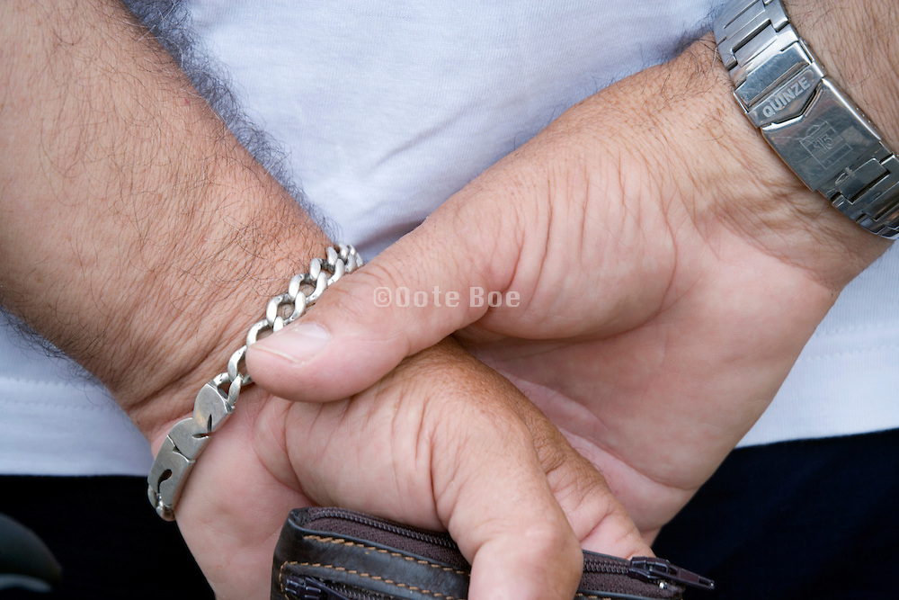 person whom has clasped his hand behind his back holding a wallet