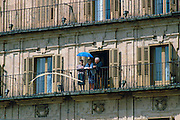 A group of elderly people standing on their balcony shielding themselves from the sun with a parasol, Salamanca, Spain