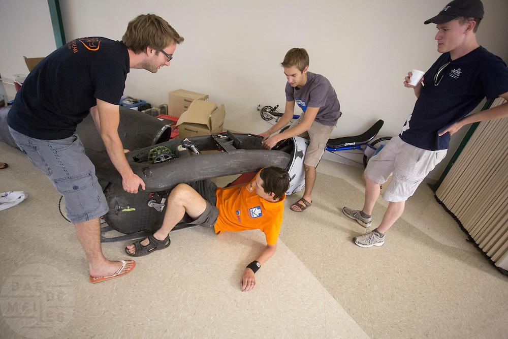 David Wielemaker van het HPT probeert in de fiets van de universiteit van Toronto te komen. Het Human Power Team Delft en Amsterdam (HPT), dat bestaat uit studenten van de TU Delft en de VU Amsterdam, is in Amerika om te proberen het record snelfietsen te verbreken. Momenteel zijn zij recordhouder, in 2013 reed Sebastiaan Bowier 133,78 km/h in de VeloX3. In Battle Mountain (Nevada) wordt ieder jaar de World Human Powered Speed Challenge gehouden. Tijdens deze wedstrijd wordt geprobeerd zo hard mogelijk te fietsen op pure menskracht. Ze halen snelheden tot 133 km/h. De deelnemers bestaan zowel uit teams van universiteiten als uit hobbyisten. Met de gestroomlijnde fietsen willen ze laten zien wat mogelijk is met menskracht. De speciale ligfietsen kunnen gezien worden als de Formule 1 van het fietsen. De kennis die wordt opgedaan wordt ook gebruikt om duurzaam vervoer verder te ontwikkelen.<br /> <br /> David Wielemakers of HPT tries to get in the Eta Speedbike of the university of Toronto. The Human Power Team Delft and Amsterdam, a team by students of the TU Delft and the VU Amsterdam, is in America to set a new  world record speed cycling. I 2013 the team broke the record, Sebastiaan Bowier rode 133,78 km/h (83,13 mph) with the VeloX3. In Battle Mountain (Nevada) each year the World Human Powered Speed Challenge is held. During this race they try to ride on pure manpower as hard as possible. Speeds up to 133 km/h are reached. The participants consist of both teams from universities and from hobbyists. With the sleek bikes they want to show what is possible with human power. The special recumbent bicycles can be seen as the Formula 1 of the bicycle. The knowledge gained is also used to develop sustainable transport.
