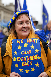 "© Licensed to London News Pictures. 30/01/2020. London, UK. A Pro-European supporter hold a ""WE WANT OUR CONTINENT BACK"" sign outside Houses of Parliament on the day before Brexit Day.  The UK will leave the European Union at 11pm on the 31 January 2020. Thereafter will be a transition period until the end of 2020, while the UK and EU negotiate additional arrangements. Photo credit: Dinendra Haria/LNP"