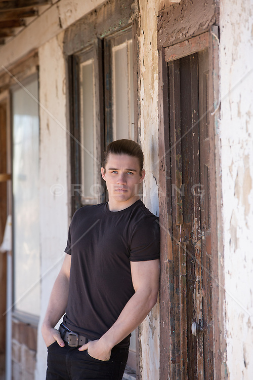 good looking man with pulled back hair against an abandoned building