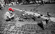 Boy in cap feeding pigeons, Piazza Navona, Rome, Italy