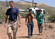 BORSTAR agent, Kelly Kirby, left, accompanies survivors, Filiberto Coronel Molina and Tomas Gomez Hernandez, to a rescue and recover command center in Silverbell, Arizona, USA. The two were part of a group of 19 illegal immigrants who ran out of water after walking for days in temperatures exceeding 105 degrees on the Tohono O'odham Nation. One known fatality resulted from heat and dehydration.