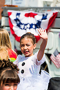Waving girl enjoying Fourth of July parade in Ames, Iowa