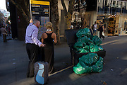A smartly-dressed couple examine a map of London streets near rubbish bags in Long Acre in Long Acre, Covent Garden in the heart of the capital's west end. With their backs to the viewer, we see the man holding an upright suitcase while his partner wearing a formal evening dress reads the map in detail. The green bags provided by Westminster city council are piled to high and spill out on to the pavement (sidewalk)