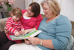 Toddler with her mum and grandmother on a sofa reading a book