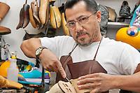 Portrait of a skilled shoemaker cutting shoe sole