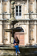Spanish girl using cellphone by Colexio de San Clemente de Pasantes in Santiago de Compostela, Galicia, Spain