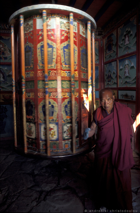 Turning the large prayer wheel at the end of the pilgrims route..LAMBRANG MONASTERY IN XIAHE - CHINA.copyright: Androniki Christodoulou.