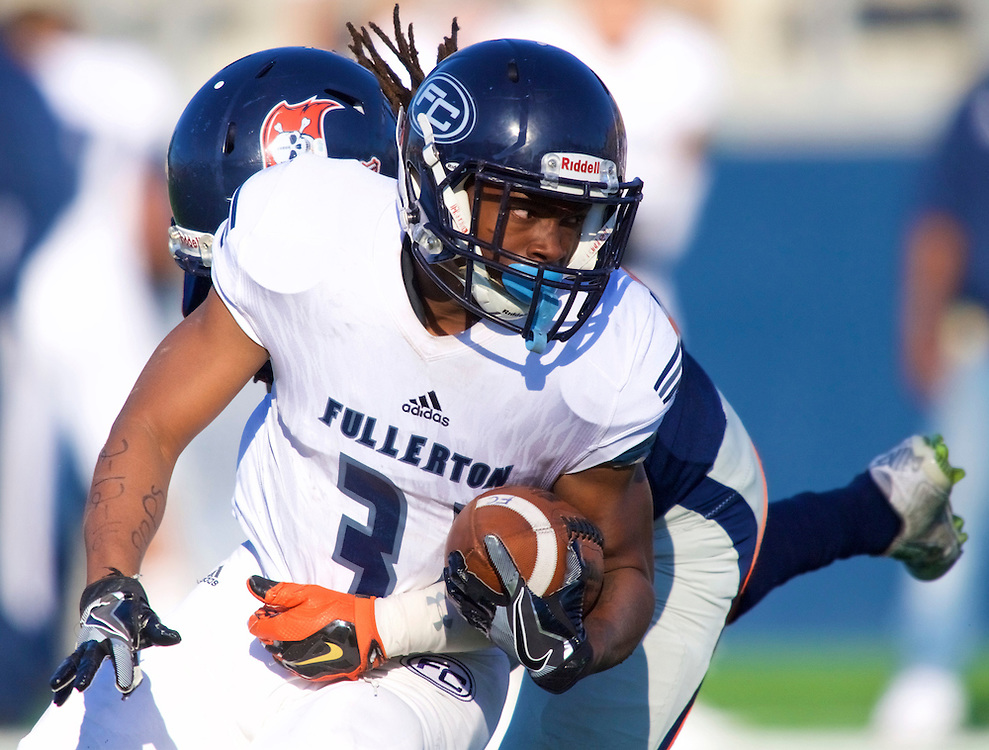 11/5/16 &ndash; Football &ndash;<br /> <br /> Fullerton Hornet running back Aundre Carter (33) fights for extra yards as he's wrapped up by Orange Coast Pirate linebacker Melvin Irby (34) during the fourth quarter of their game at Orange Coast College in Costa Mesa, Calif, Nov. 5, 2016.<br /> <br /> Photo by Seth Laubinger / Sports Shooter Academy