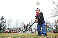 Gregory Bauerle, 3, keeps his eye on the ball after his father, Kevin Bauerle, threw the pitch Tuesday during an afternoon visit to G.O. Phippeny Park in Coeur d'Alene.