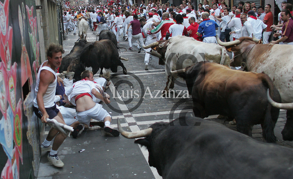 Participants run ahead of Fuente Ymbro fighting on July 9, 2008 during the sixth running of the bulls of the San Fermin festivities through the northern Spanish city of Pamplona. The running of the bulls take place at 8 a.m. (0600 GMT) on each day of the centuries-old festival, which is also known for its all-night street parties that attract tourists from around the worldPamplona 9-07-2008 Unos mozos son arrollados por los toros de Fuente Ymbro en la curva de mercaderes. Foto Luis Azanza