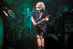 Jerry Garcia playing and singing in shorts. With The Grateful Dead on 1 October 1994 at The Boston Garden