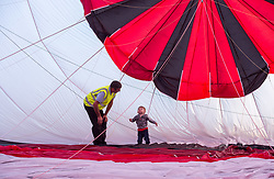 © Licensed to London News Pictures. 29/07/2019; Bristol, UK. Press preview flight for the 41st Bristol International Balloon Fiesta 2019 which will take place from 08 - 11 August 2019. Pilot Craig Thompson for Ben's Tiles Balloons checks inside the balloon envelope before take off with his son Freddie aged 21 months. For the preview up to 25 hot air balloons will take off from Filton Airfield, next to the Brabazon Hangar which is the site of a proposed new YTL Arena, and Aerospace Bristol to play homage to the 50th anniversary of Concorde. The Bristol International Balloon Fiesta attracts hundreds of thousands of visitors and this year the Fiesta will be celebrating Icons of Bristol and look to highlight some of the things that make up the home of the International Balloon Fiesta. The event has joined forces with Aerospace Bristol to honour one of the city's most famed creations, Concorde and Aardman Animations who are celebrating the 30th anniversary of Wallace and Gromit. Over the course of four days, the Bristol International Balloon Fiesta will play host to more than 100 colourful hot air balloons of all sizes and shapes. Special shapes are an iconic part of the Fiesta and the event kicks off with its now traditional special shapes launch on Thursday evening of 08 August. Photo credit: Simon Chapman/LNP.